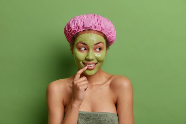 Mulher jovem e feliz e sonhadora enrolada em uma toalha de banho, mostrando os ombros nus, sorrindo, com os dentes, preocupados com a pele, aplicando uma máscara de beleza isolada sobre uma parede verde vívida