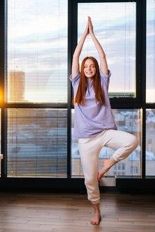 Mulher jovem e feliz e tranquila praticando ioga em pé na postura da árvore vrksasana em pé perto da janela