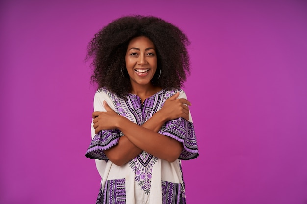 Mulher jovem e feliz encaracolada com pele escura, vestindo uma camisa branca estampada, posando em roxo com as mãos cruzadas no peito, alegre e com um sorriso largo