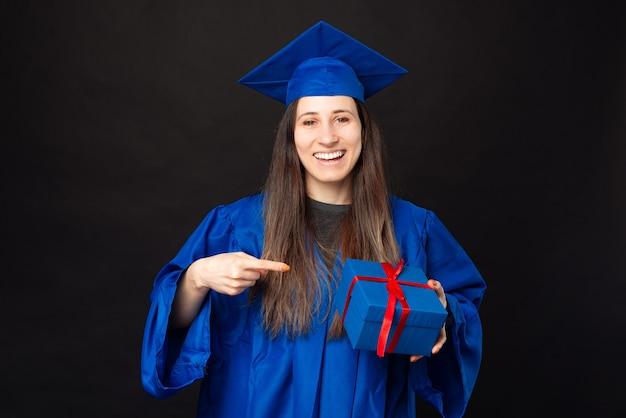 Mulher jovem e feliz estudante apontando para uma caixa de presente e vestindo um solteiro azul