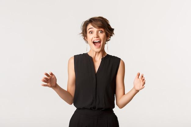 Mulher jovem e feliz impressionada mostrando um grande objeto, segurando o produto.