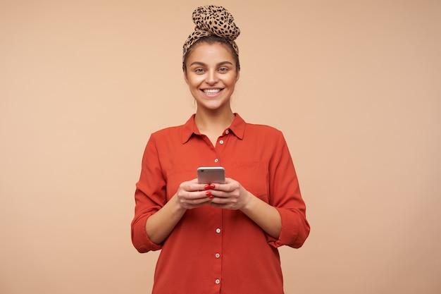 Mulher jovem e feliz, morena de olhos verdes, sorrindo alegremente na frente e mantendo o smartphone nas mãos levantadas enquanto está de pé sobre uma parede bege