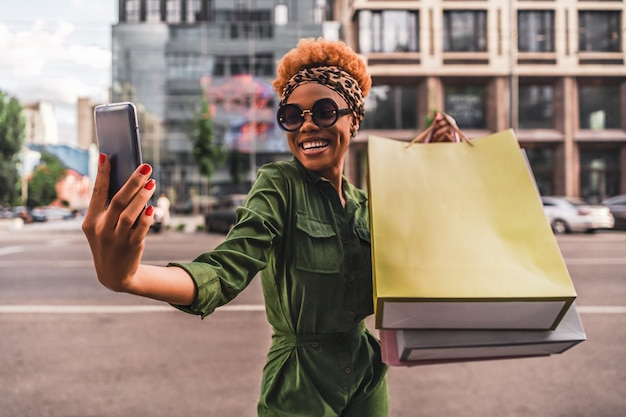 Mulher jovem e feliz na moda fazendo selfie no smartphone e segurando sacolas de compras na cidade