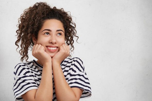 Mulher jovem e feliz parece com uma expressão sonhadora, sorri amplamente, mantém as mãos embaixo do queixo