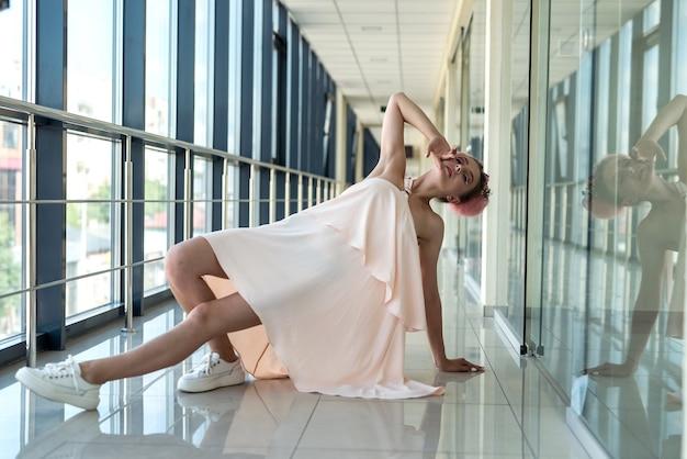 Mulher jovem e feliz posando no corredor de um edifício
