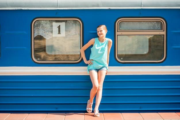 Mulher jovem e feliz, puxando o rosto para fora da porta do trem à procura de alguém na estação ferroviária