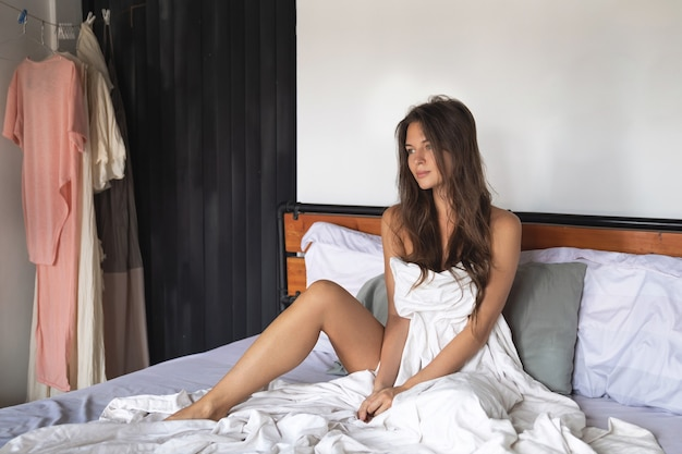 Mulher jovem e feliz relaxando na cama