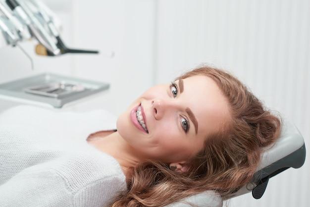Mulher jovem e feliz ruiva com aparelho e sorrindo, sentada em uma cadeira odontológica