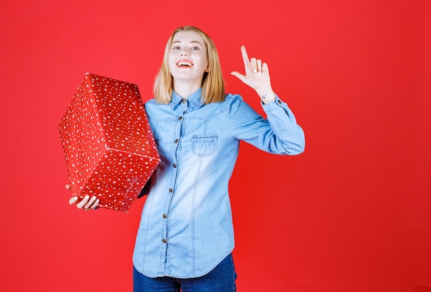 Mulher jovem e feliz segurando o presente de aniversário e apontando para cima em uma parede vermelha