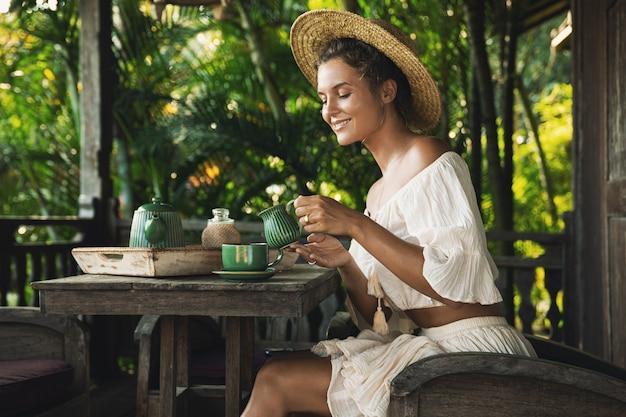 Mulher jovem e feliz sentada na esplanada a beber café