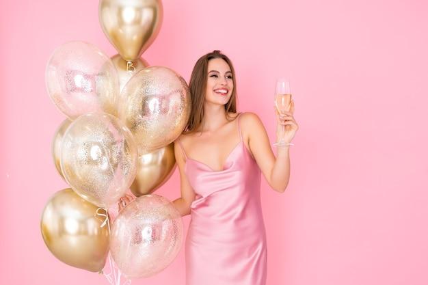 Mulher jovem e feliz sorridente levanta uma taça de champanhe e celebra balões de ar dourados