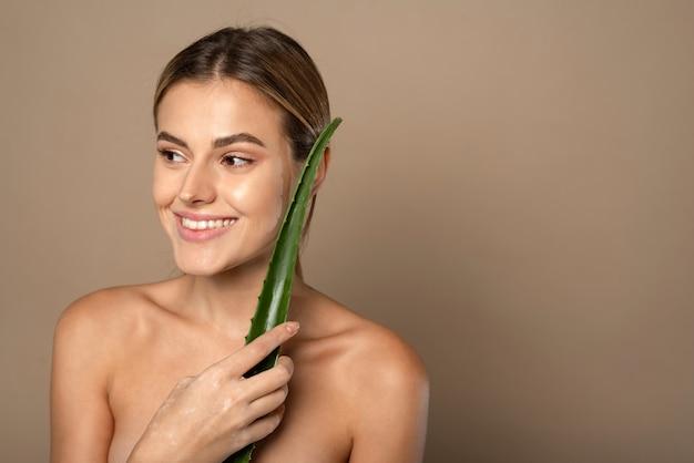 Mulher jovem e feliz sorridente segurando folha de aloe vera nas mãos em bege