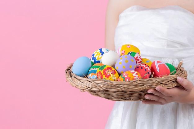 Mulher jovem e feliz sorrindo com orelhas de coelho e segurando um dos ovos de páscoa no fundo rosa