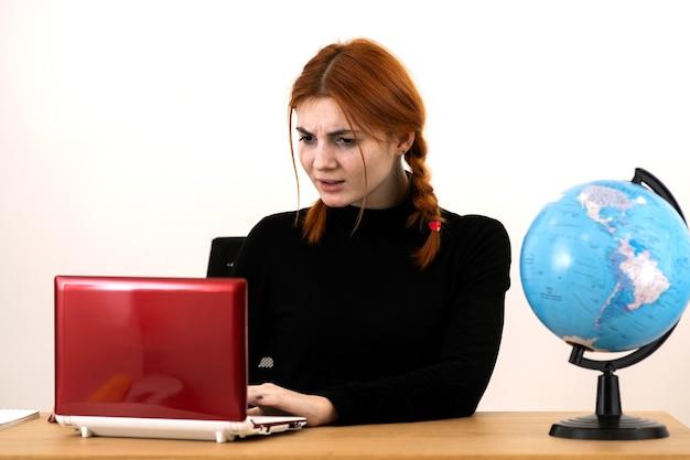 Mulher jovem e feliz trabalhadora de escritório sentada atrás de uma mesa de trabalho com um laptop