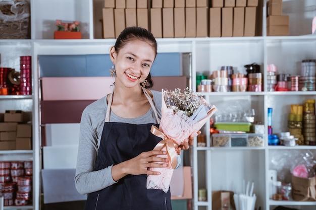 Mulher jovem e feliz trabalhando em uma floricultura usando avental e segurando flores de flanela