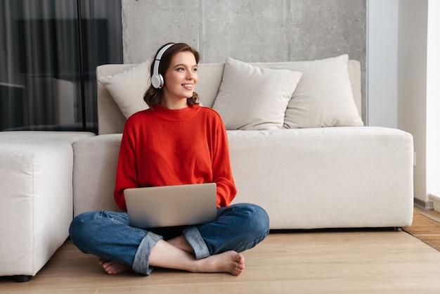 Mulher jovem e feliz vestida de maneira casual, sentada no chão de casa, estudando com um laptop
