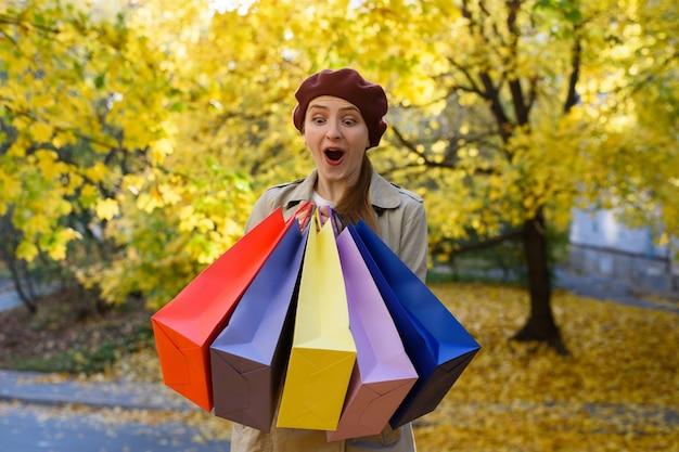 Mulher jovem e feliz, viciada em compras com sacolas coloridas perto de shopping