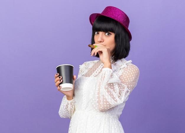 Mulher jovem e festeira impressionada com chapéu de festa em pé na vista de perfil, segurando a chifre de festa na boca e a xícara de café de plástico na outra mão, olhando para a frente, isolada na parede roxa