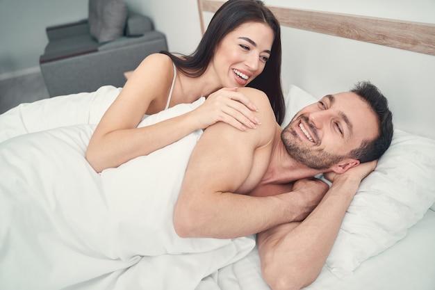 Mulher jovem e fofa alegre com cabelo escuro solto olhando para o marido sorridente na cama