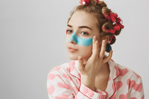 Mulher jovem e fofa feminina em rolos de cabelo e pijamas aplicar máscara facial
