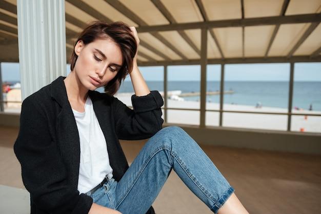 Mulher jovem e fofa relaxada sentada em um gazebo perto do mar