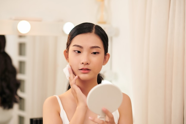 Mulher jovem e fofa removendo a maquiagem, limpando o rosto com almofadas de algodão, olhando no espelho
