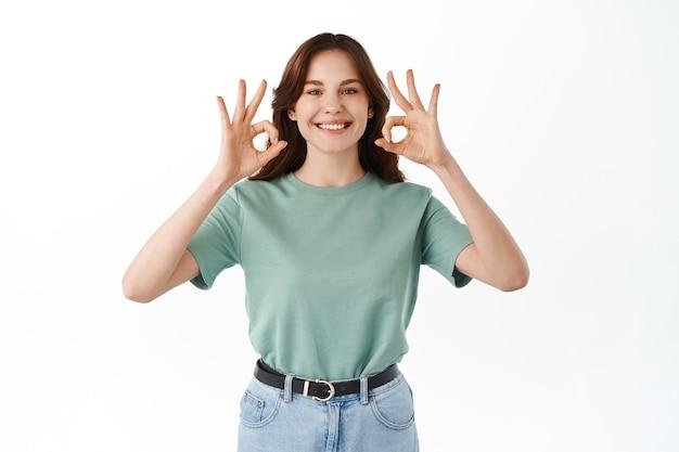Mulher jovem e fofa sorridente em uma camiseta mostra seu apoio, faz sinais de ok e acena com a cabeça em aprovação, concorda ou aprova, recomenda o produto, encostada na parede branca