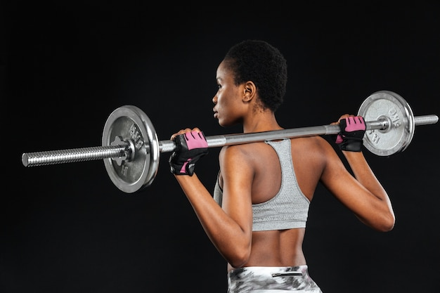 Mulher jovem e forte com belo corpo atlético fazendo exercícios com barra isolada em uma parede preta