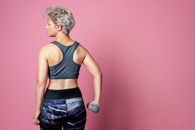 Mulher jovem e forte e ativa segurando halteres para musculação