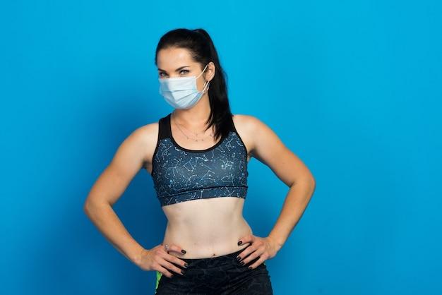 Mulher jovem e forte em uma máscara facial malhando isolada em um estúdio de parede azul