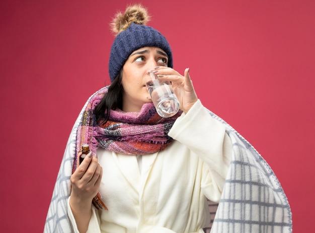 Mulher jovem e fraca, caucasiana, doente, vestindo manto, chapéu e lenço de inverno, bebendo um copo de água misturado com medicamento