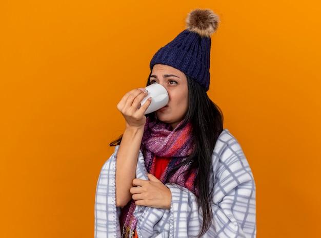 Mulher jovem e fraca, doente, usando chapéu de inverno e cachecol embrulhado em uma manta em pé em vista de perfil, bebendo uma xícara de chá, olhando diretamente isolado na parede laranja
