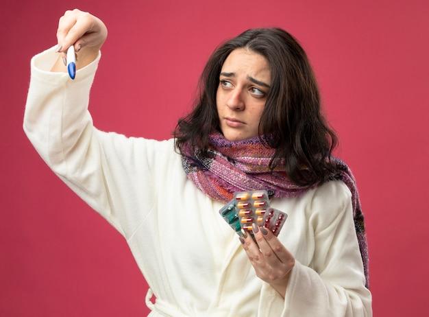 Mulher jovem e fraca, doente, usando manto e lenço segurando pacotes de cápsulas médicas e termômetro, olhando para o termômetro isolado na parede rosa