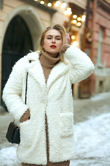 Mulher jovem e glamorosa com casaco de pele e bolsa andando pela rua no inverno