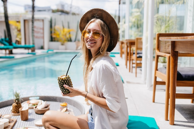 Mulher jovem e glamorosa olhando por cima do ombro enquanto bebia um coquetel de abacaxi. menina loira sorridente com chapéu, sentado perto da piscina com frutas.