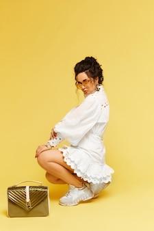 Mulher jovem e glamourosa modelo usando um vestido branco e óculos de sol da moda, posando com uma bolsa dourada.