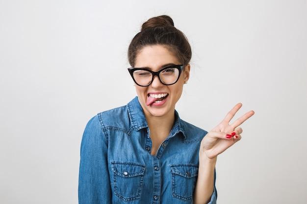 Mulher jovem e hippie elegante com óculos da moda e camisa jeans, fazendo uma expressão de careta engraçada, mostrando a língua, piscando, gesto de paz, positivo