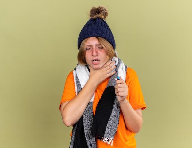 Mulher jovem e insalubre com chapéu e lenço em volta do pescoço, sentindo-se mal, segurando diferentes comprimidos, sofrendo de dor de garganta, tocando, sentindo dor, pescoço, em pé, sobre a parede verde