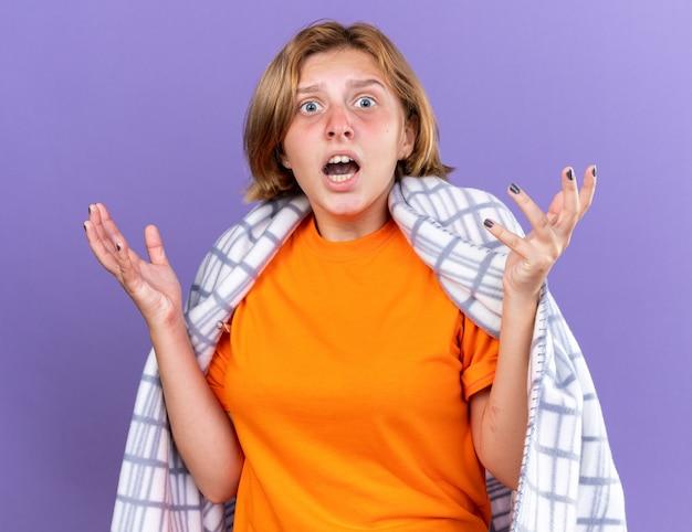 Mulher jovem e insalubre confusa, enrolada em um cobertor quente, sentindo-se doente, sofrendo de gripe, tendo febre medindo sua temperatura usando um termômetro, parecendo preocupada, levantando os braços na parede roxa