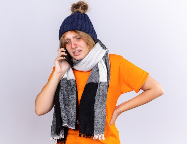 Mulher jovem e insalubre em uma camiseta laranja com um cachecol quente em volta do pescoço e um chapéu, sentindo-se terrível, sofrendo de gripe, falando no celular com uma expressão triste