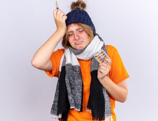 Mulher jovem e insalubre em uma camiseta laranja com um lenço quente em volta do pescoço e um chapéu, sentindo-se terrivelmente sofrendo de gripe segurando uma seringa e pílulas chorando