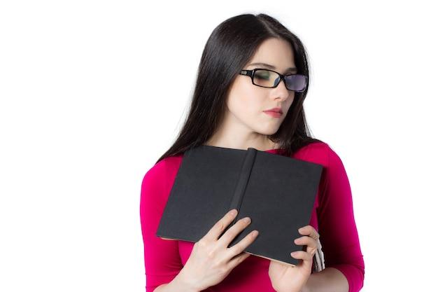 Mulher jovem e inteligente estudante de camisa vermelha e óculos pressionando o livro preto contra o coração mulher sonhadora