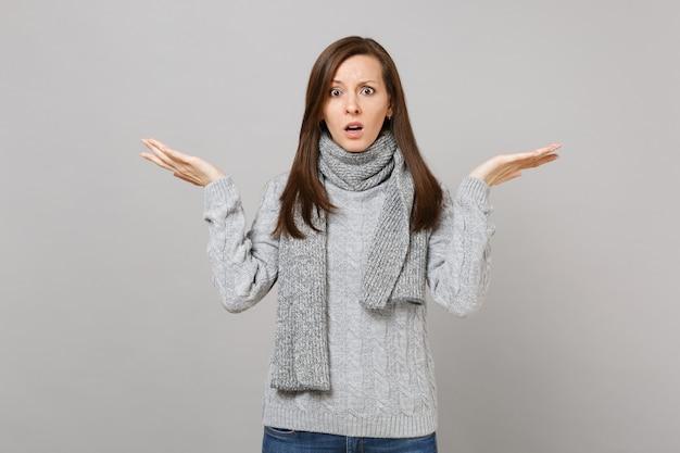 Mulher jovem e intrigada chocada em um cachecol de suéter cinza espalhando as mãos isoladas no fundo da parede cinza no estúdio. conceito de estação fria de emoções sinceras de pessoas de estilo de vida de moda saudável. simule o espaço da cópia.