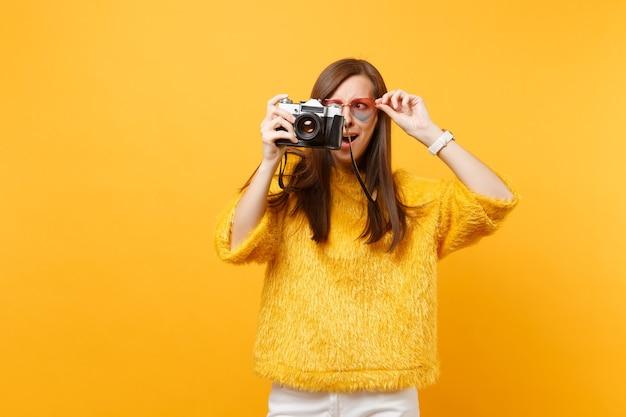 Mulher jovem e intrigada chocada segurando óculos de coração e tirando fotos na câmera fotográfica vintage retrô isolada em fundo amarelo brilhante. emoções sinceras de pessoas, conceito de estilo de vida. área de publicidade.