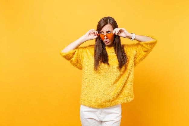 Mulher jovem e intrigada preocupada em um suéter de pele, calça branca segurando óculos coração laranja olhando de lado isolado no fundo amarelo brilhante. emoções sinceras de pessoas, conceito de estilo de vida. área de publicidade.