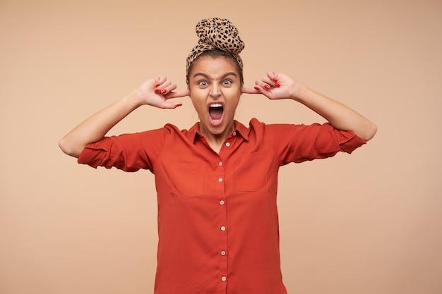 Mulher jovem e irritada de cabelos castanhos, de olhos verdes, gritando estressadamente enquanto tapava as orelhas com o dedo indicador, em pé sobre uma parede bege em trajes casuais