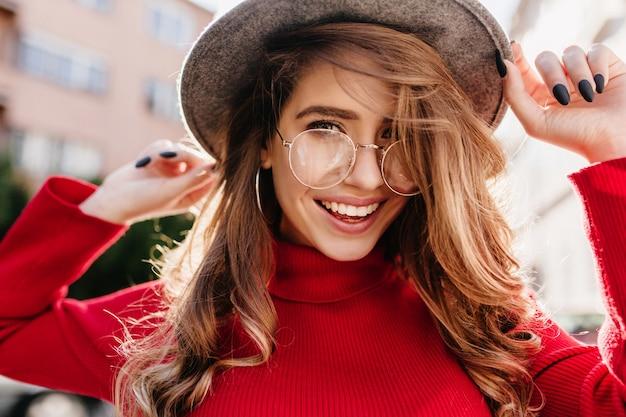 Mulher jovem e linda com sorriso sincero, posando de óculos em um dia ensolarado de outono