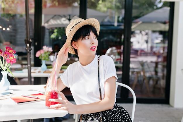Mulher jovem e linda com um penteado da moda relaxando em um restaurante ao ar livre e olhando para longe enquanto bebe um coquetel