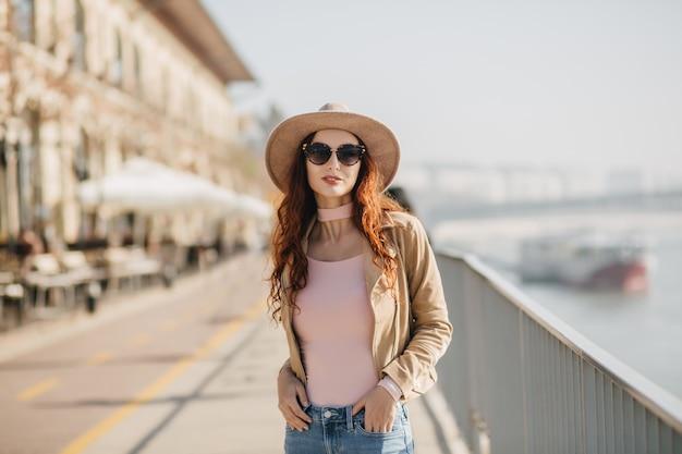 Mulher jovem e linda em óculos de sol escuros, em pose confiante no aterro