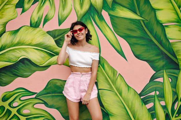 Mulher jovem e linda em shorts em frente a um grafite verde
